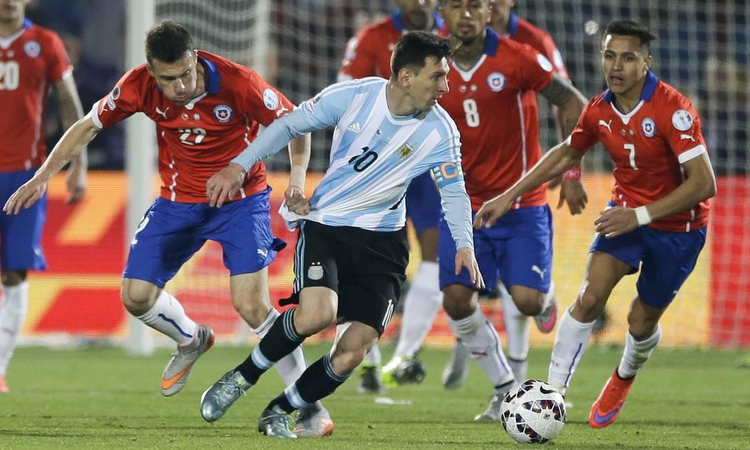 O chileno Angelo Henriquez puxa a camisa de Messi; foi o jeito que encontrou para tentar conter o craque argentino Ricardo Mazalan / AP