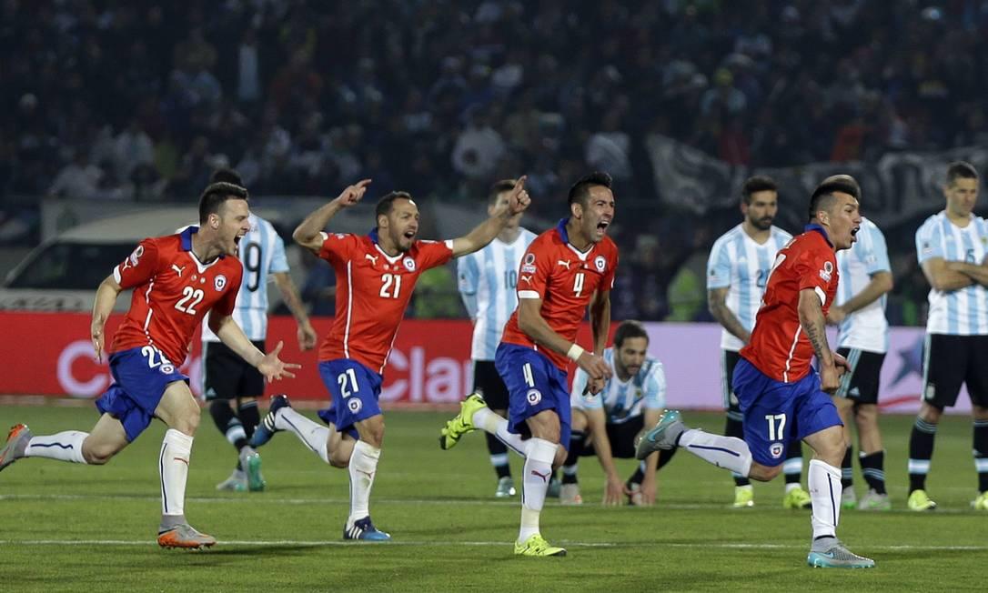 Diante dos decepcionados jogadores argentinos, os chilenos correm para festejar após a defninição na cobrança de pênaltis: campeões em casa Natacha Pisarenko / AP