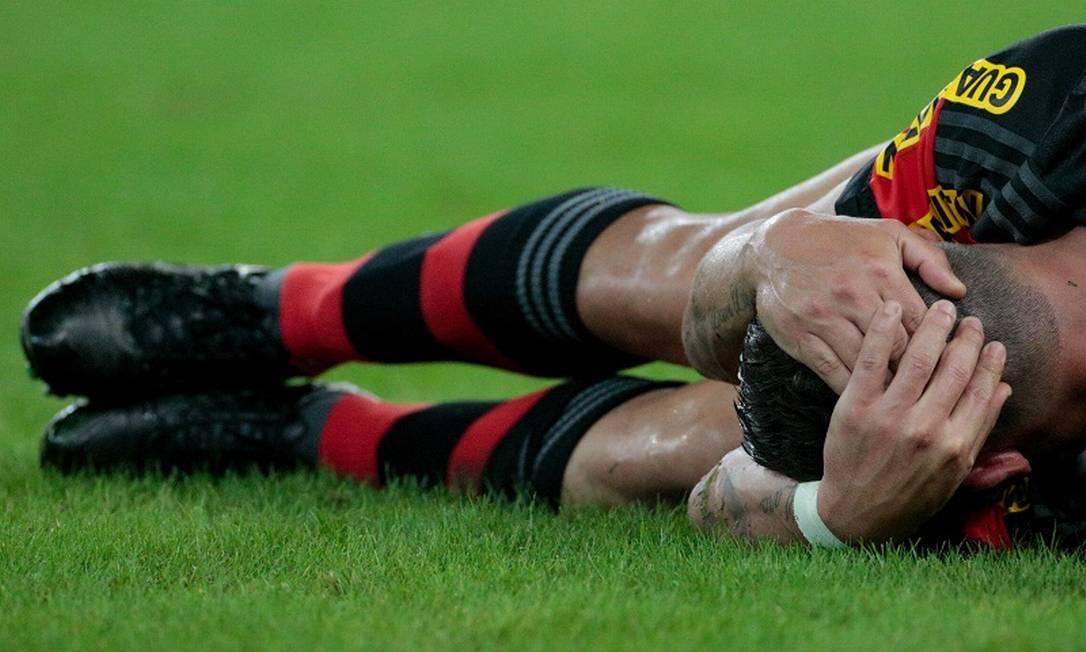 O lateral Ayrton fica no chão após ser atingido por uma joelhada na cabeça na derrota do Flamengo para o Figueirense Pedro Kirilos / Agência O Globo
