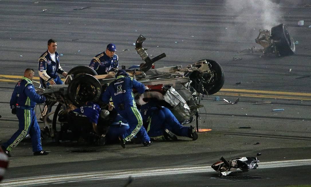 Membros da equipe tentam tirar Austin Dillon de dentro do carro após o acidente Patrick Smith / AFP