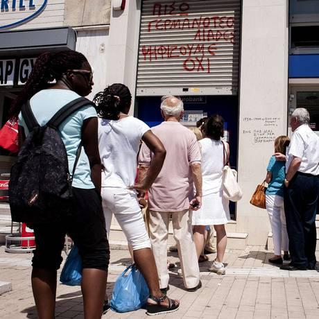 Com bancos fechados, gregos fazem fila em frente a caixa eletrônico em Atenas Foto: IAKOVOS HATZISTAVROU / AFP