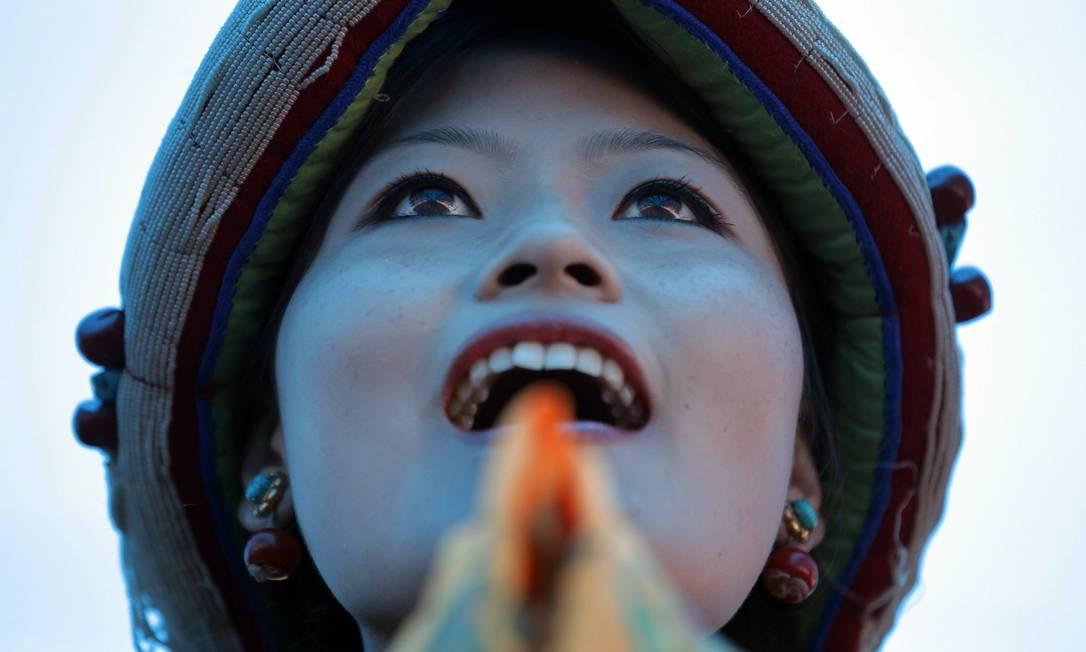 Mulher de Katmandu, no Nepal, canta em comemoração aos 80 anos do Dalai Lama, comemorado neste domingo Niranjan Shrestha / AP