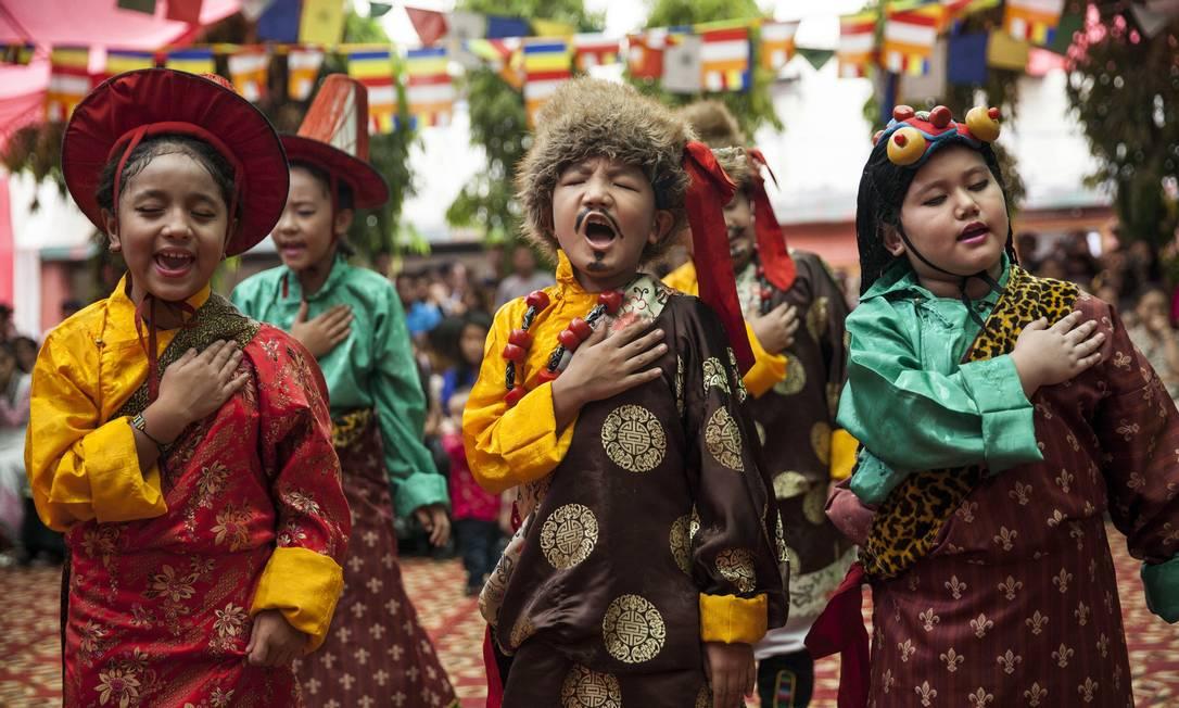 Numa escola para exilados tibetanos, crianças vestidas com roupa tradicional cantam para saudar o líder religioso Tsering Topgyal / AP