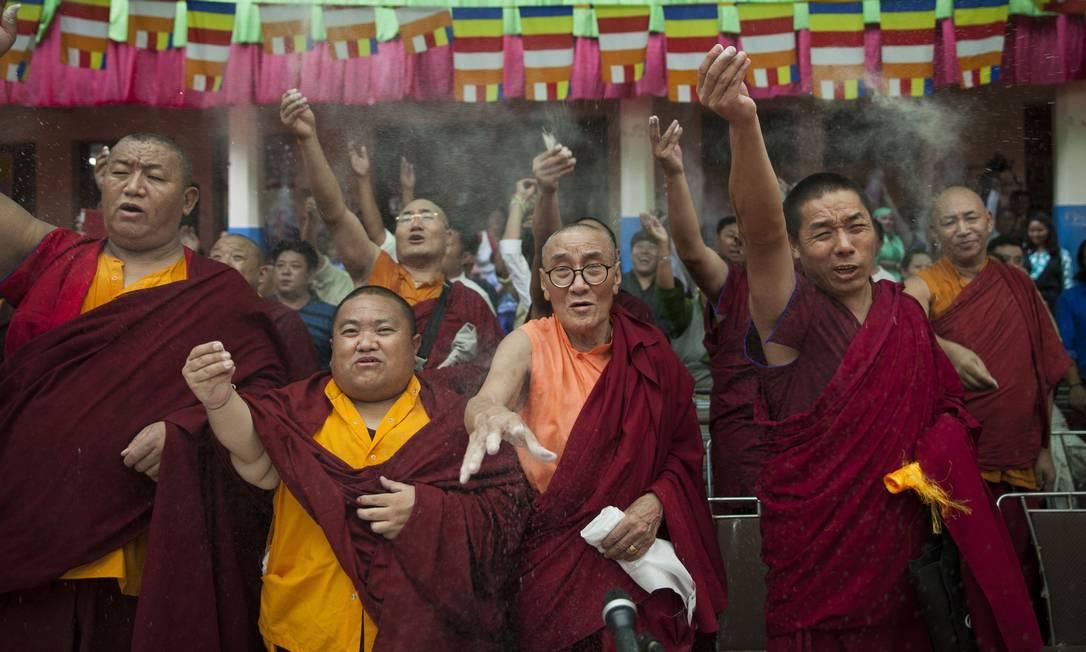 Monges tibetanos exilados atiram cevada ao ar para comemorar os 80 anos de seu líder Tsering Topgyal / AP