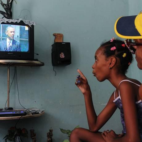 Cubanos acompanham Obama em sua TV: políticas americanas vão lentamente mudando em relação à ilha Foto: YAMIL LAGE / AFP