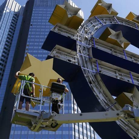 Funcionários do BCE desmontam o símbolo do euro em Frankfurt Foto: RALPH ORLOWSKI / REUTERS