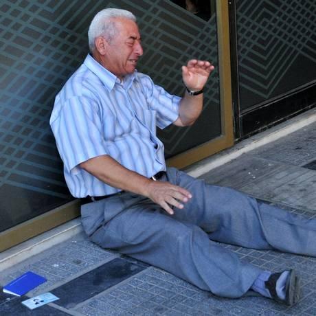 Giorgos Chatzifotiadis, chora em frente a uma agência bancária da cidade de Thessaloniki, após saber que só poderia retirar 60 euros de sua conta Foto: SAKIS MITROLIDIS / AFP