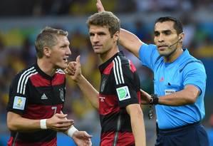 Marco Rodriguez com Thomas Müller e Schweinsteiger durante o jogo no Mineirão Foto: PEDRO UGARTE / AFP