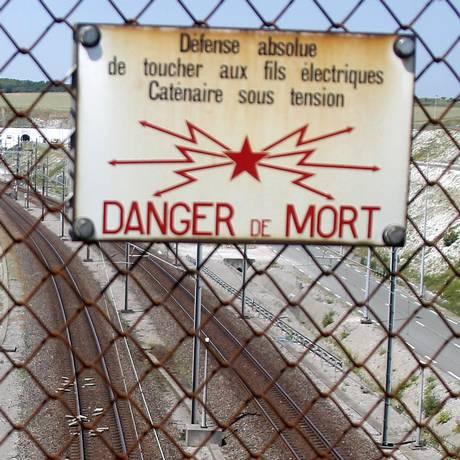 Perigo. Um cartaz adverte sobre o risco de morte no caminho de ferro no túnel sob o Canal da Mancha Foto: Michel Spingler / AP / 30/06/2015