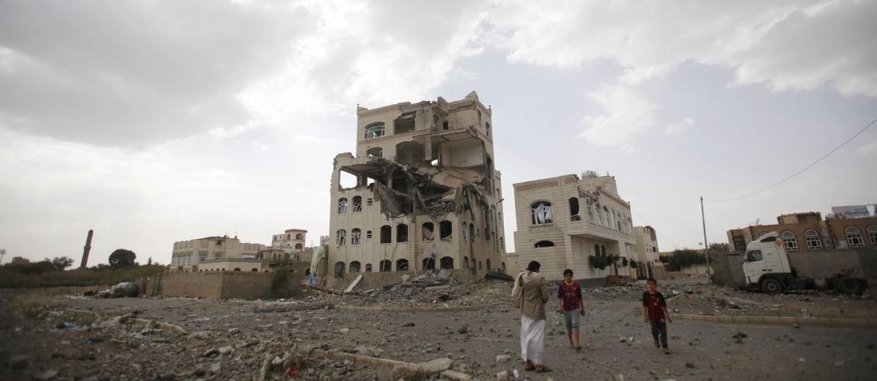 Destruição. Pessoas próximas a um edifício destruído por um ataque aéreo em Sanaa, capital do Iêmen, liderado pela Arábia Saudita Foto: Hani Mohammed / AP / 06/07/2015