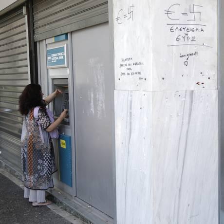 Mulheres sacam dinheiro em caixa eletrônico em Atenas Foto: Petr David Josek / AP