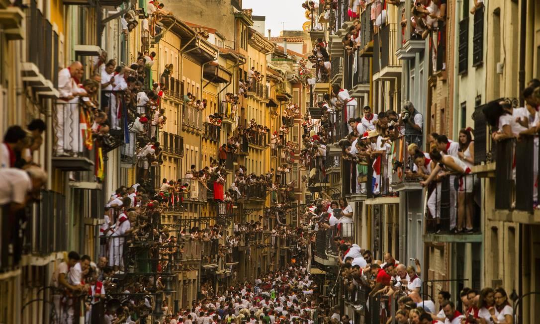 Turistas observam a corrida de suas janelas e varandas, em um cenário único de lotação Andres Kudacki / AP