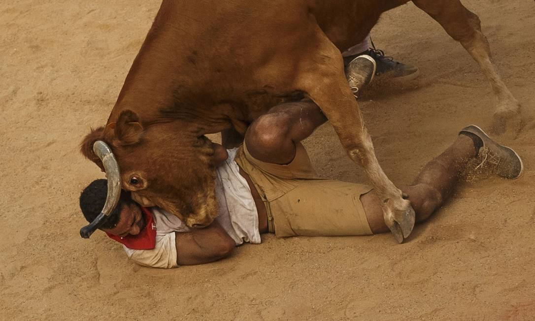 Homem cai no chão ao ser derrubado por um touro enquanto participava do festival Daniel Ochoa de Olza / AP