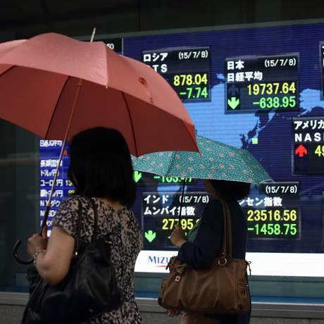 Pedestres passam em frente a painel eletrônico em Tóquio com o resultado das principais Bolsas do mundo Foto: Tomohiro Ohsumi / Bloomberg News