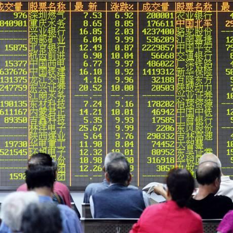 Investidores acompanham a movimentação no mercado em corretora de Hangzhou, na província de Zhejiang, no Leste da China Foto: STR / AFP