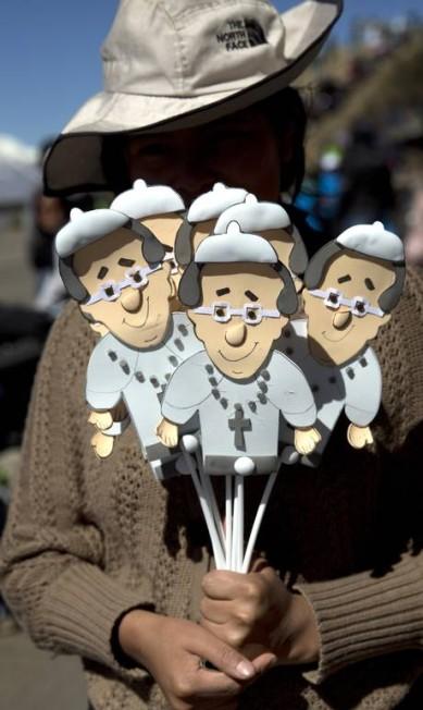 Vendedor de rua oferece bonecos de papelão com o rosto do Papa Rodrigo Abd / AP