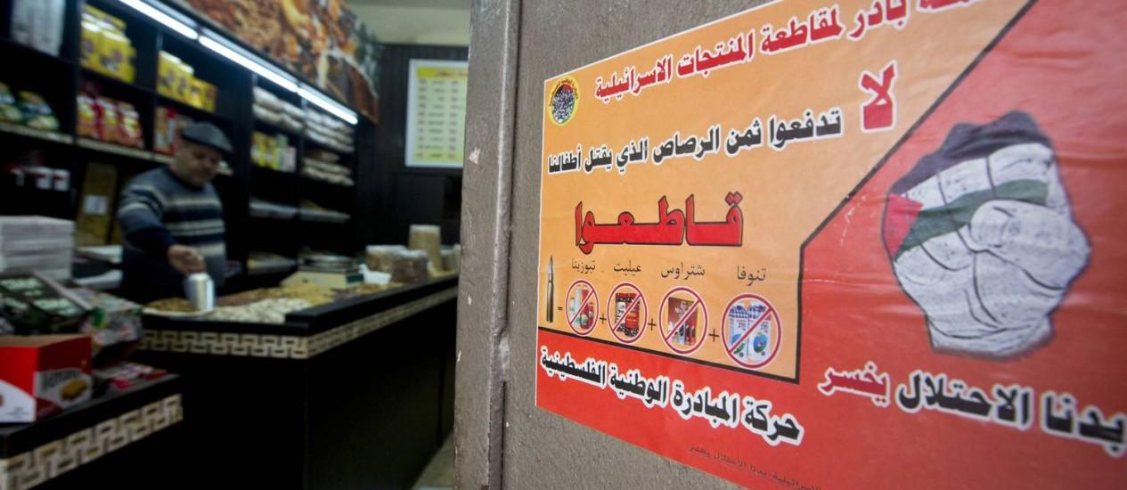 Em um mercado na cidade de Ramallah, na Cisjordânia, um cartaz convoca as pessoas a boicotarem produtos israelenses Foto: Majdi Mohammed / AP