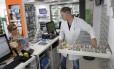 Em uma farmácia de Atenas, funcionário procura medicamento para cliente