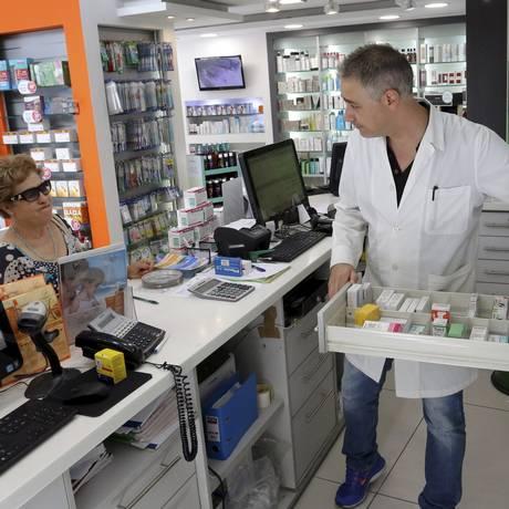 Em uma farmácia de Atenas, funcionário procura medicamento para cliente Foto: STEFANOS RAPANIS / REUTERS