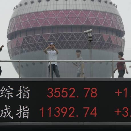 Pessoas caminham sobre painel eletrônico em Xangai que exibe o desempenho do mercado financeiro Foto: Chinatopix / AP