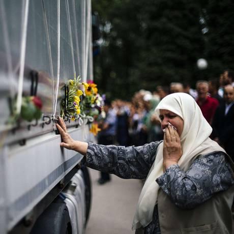 Mulher bósnia chora enquanto toca caixão de uma das vítimas do massacre de Srebrenica Foto: DIMITAR DILKOFF / AFP