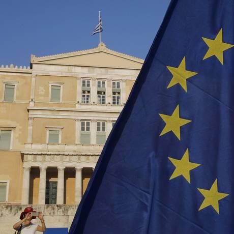 Mulher fotografa bandeira da União Europeia, que tremula em frente ao Parlamento grego, em Atenas Foto: YANNIS BEHRAKIS / REUTERS