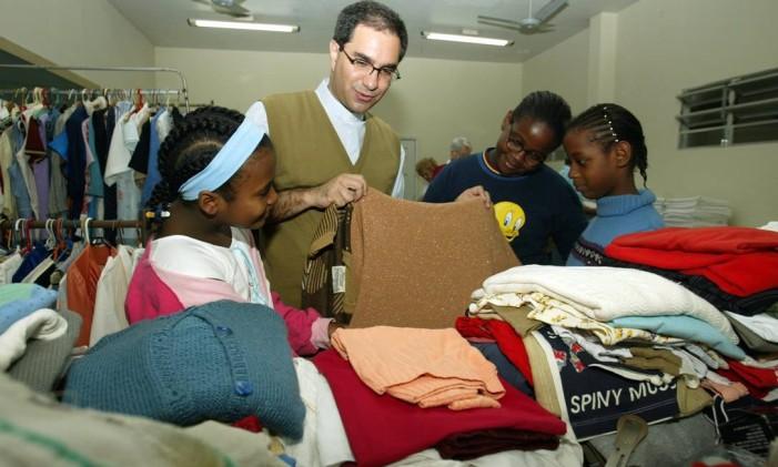 Crianças observam agasalhos doados Foto: André Teixeira / Agência O Globo (04/06/2004)