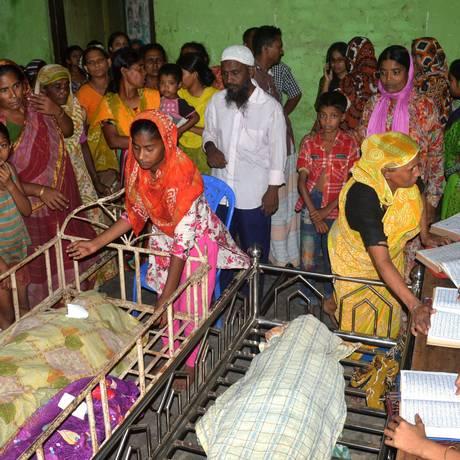 Parentes observam corpos de pessoas pisoteadas em um evento de caridade em Bangladesh Foto: AFP