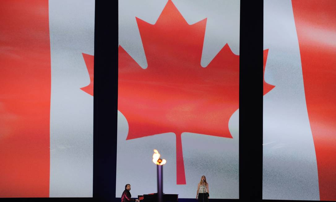 A bandeira do país anfitrião é exibida em um telão HECTOR RETAMAL / AFP