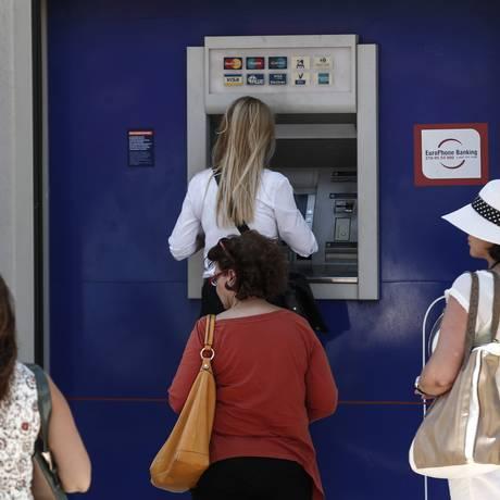Gregos fazem fila para retirar dinheiro de caixa eletrônico em agência fechada do Eurobank em Atenas Foto: Yorgos Karahalis / Bloomberg