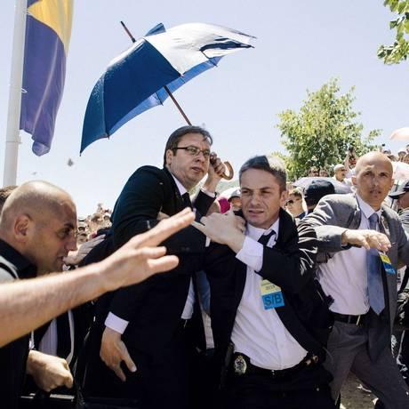 O premier Aleksandar Vucic é protegido por segurança em cerimônia em Srebrenica Foto: DIMITAR DILKOFF / AFP
