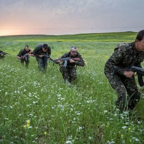 Treinamento gringo. Estrangeiros fazem aula de combate da Unidades de Proteção Popular (YPG) no Noroeste da Síria: apoio cresceu com sucesso militar contra Estado Islâmico e valores pró-ocidentais dos curdo Foto: UYGAR ONDER SIMSEK / AFP