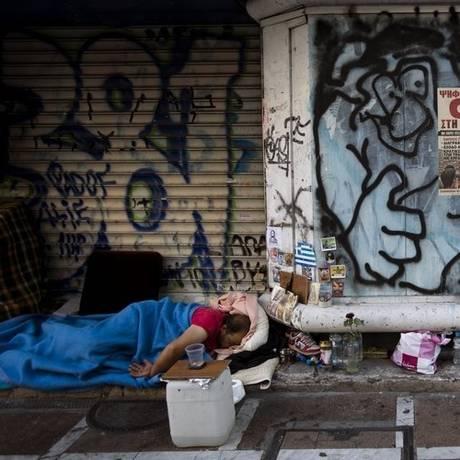 """Sem-teto. Em Atenas, homem dorme na rua, sob placa do """"não"""" ao ajuste Foto: AP/6-7-2015"""