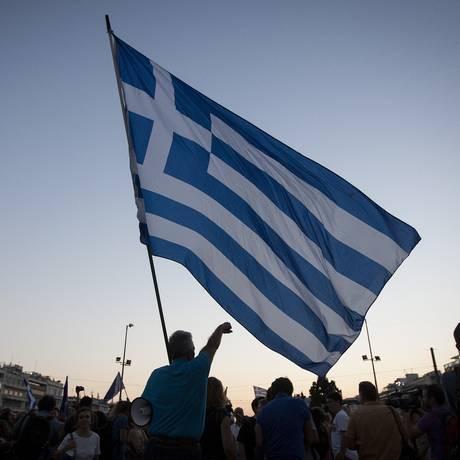 Manifestante segura bandeira grega em protesto contra austeridade Foto: Simon Dawson / Bloomberg
