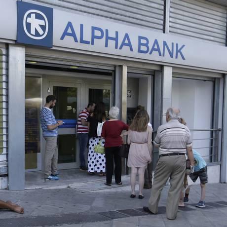 Fila em frente a um caixa eletrônico em Atenas: bancos ainda não têm data para reabrir Foto: Thanassis Stavrakis / AP