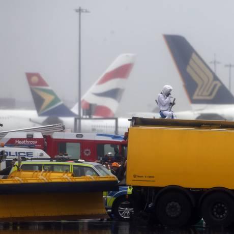 Equipes de emergência tentam tirar manifestante vestido de urso polar do alto de um caminhão na pista de Heathrow Foto: Steve Parsons / AP