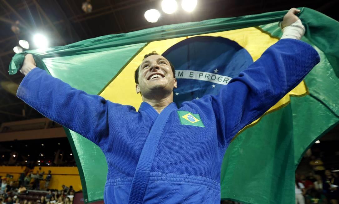 Orgulhoso, Tiago Camilo exibe a bandeira do Brasil Julio Cortez / AP