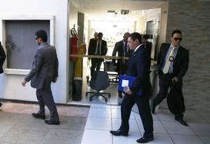 Policiais federais deixam o apartamento funcional de Fernando Collor (PTB-AL) com malotes de documentos apreendidos Foto: Ailton de Freitas / Agência O Globo