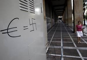 Pichação em rua de Atenas compara o símbolo do euro à suástica nazista Foto: YANNIS BEHRAKIS / REUTERS