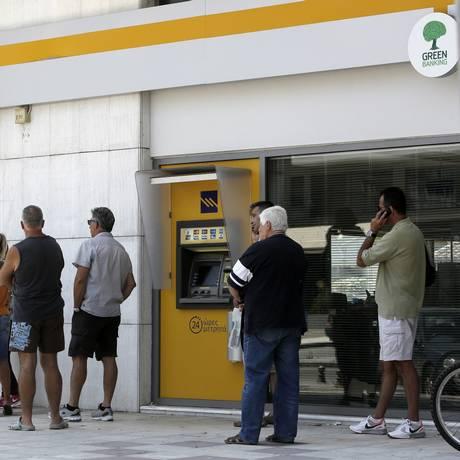 Clientes fazem fila para usar caixa eletrônicos de bancos gregos Foto: Konstantinos Tsakalidis / Bloomberg
