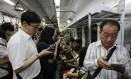 Passageiros checam seus smartphones no metrô de Seoul, na Coreia do Sul Foto: Ahn Young-joon / AP
