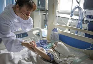 Han Han, de 3 anos, com sua tia no hospital de Changsha, província de Hunan, na China, depois da cirurgia de 17 horas que implantou três peças de malha de titânio para substituir seu crânio Foto: CHINA STRINGER NETWORK / REUTERS