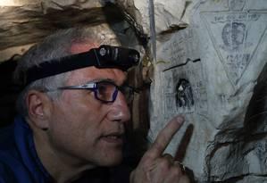 O médico Jeffrey Gusky, que passou os últimos 20 anos recolhendo imagens para o projeto 'O mundo escondido da Primeira Guerra Mundial', aponta uma das inscrições na caverna de Bouzincourt, na França Foto: PASCAL ROSSIGNOL / REUTERS