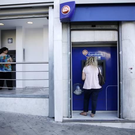 Gregos fazem retirada em caixas eletrônicos de bancos fechados, em Atenas Foto: Matthew Lloyd / Bloomberg