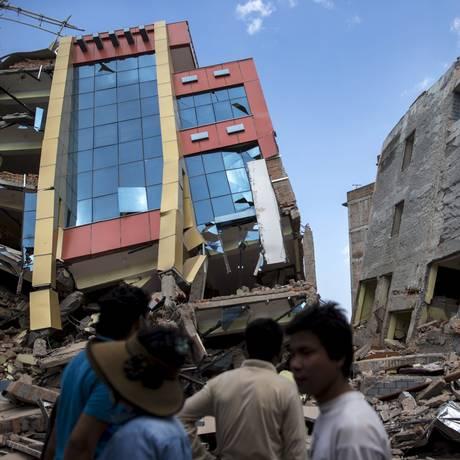 Pessoas caminham próximas aos escombros de edifícios que desabaram após um terremoto de magnitude 7,3, em maio deste ano, que abalou o Nepal Foto: Athit Pera Wongmetha / Reuters / 13/05/2015