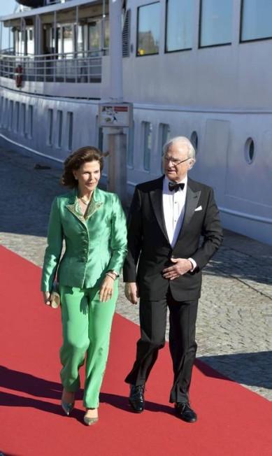 O rei da Suécia, Carl Gustaf, e a rainha Silvia, que é filha de uma brasileira, caminham em direção ao navio que levou os convidados para a festa TT NEWS AGENCY / REUTERS