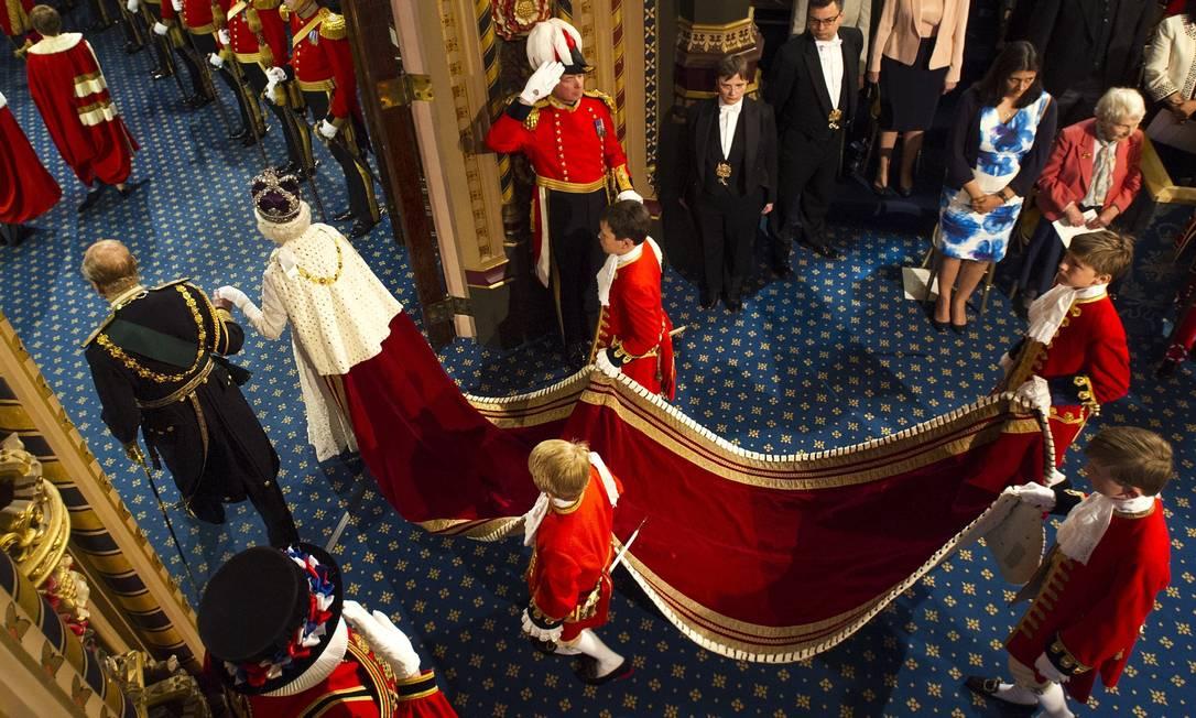Quatro pajens ajudaram a rainha a carregar o manto de veludo GEOFF PUGH / AFP