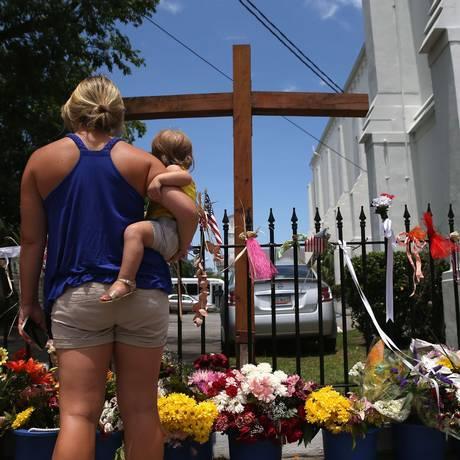 Pessoas visitam a igreja metodista de Charleston, na Carolina do Sul, onde nove pessoas foram assassinadas em um massacre Foto: John Moore / AFP / 15/07/2015
