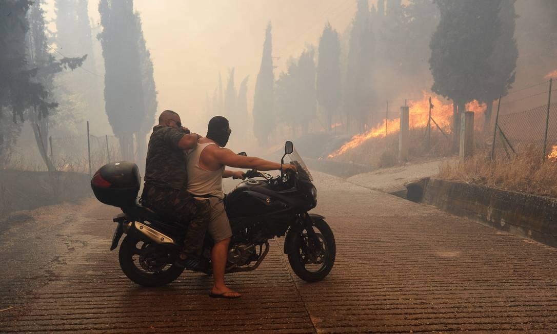Dois homens usam moto para deixar uma das áreas afetadas Giorgos Bamboukos / AP