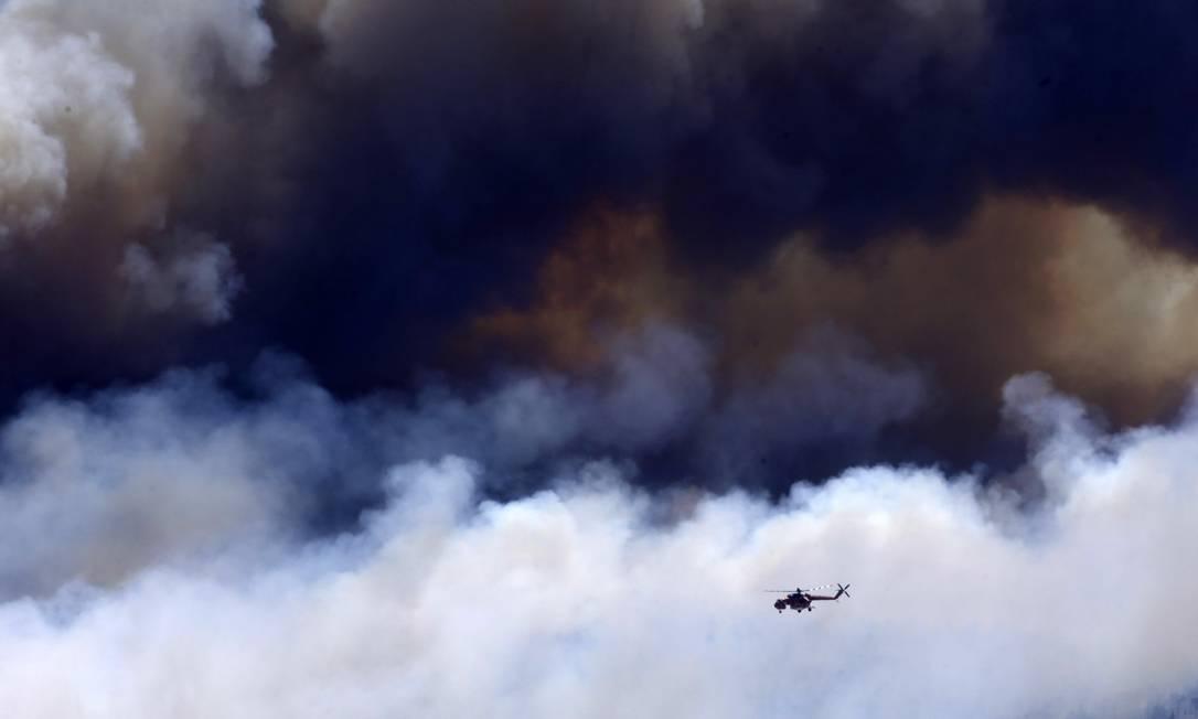 Helicóptero sobrevoa incêndio na região do Monte Yemette Petros Karadjias / AP